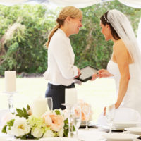 Bride With Wedding Planner In Marquee Using A Digital Tablet