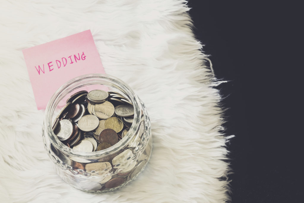 many coins in a money jar with wedding label on jar. wedding concept. saving concept