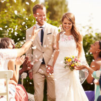 Guests Throwing Confetti Over Bride And Groom At Wedding
