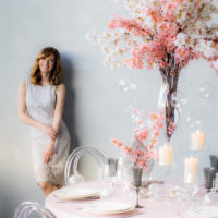 Smiling bride near the wall and wedding decorations